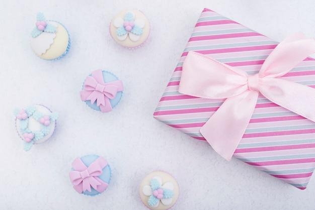 Caja de regalo envuelta brillante y pasteles decorados. Foto gratis