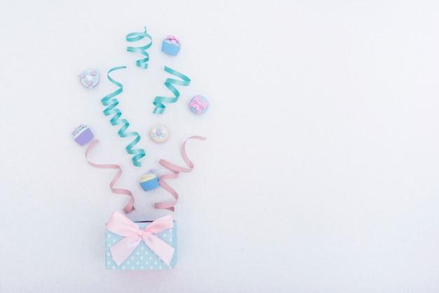 Caja de regalo festivo con cintas y cupcakes. Foto gratis