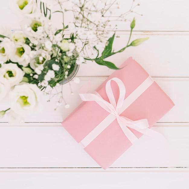 Caja de regalo con flores en florero. Foto gratis