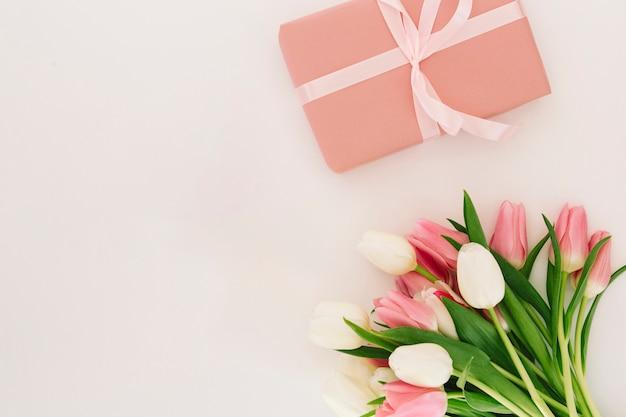 Caja de regalo con flores de tulipanes. Foto gratis