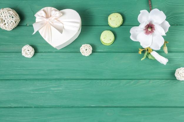 Caja de regalo en forma de corazón con flores y macarrones. Foto gratis