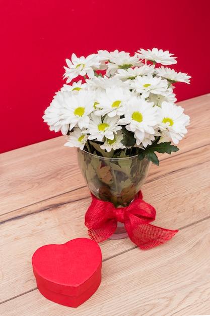 Caja de regalo en forma de corazón con ramo de flores en florero. Foto gratis
