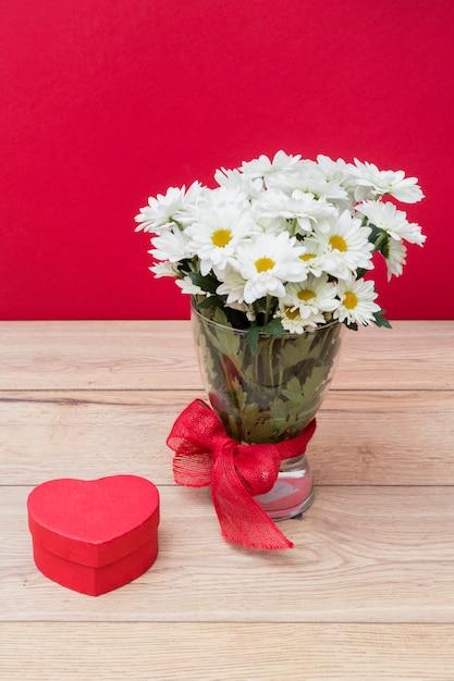Caja de regalo en forma de corazón con ramo de margaritas en florero Foto gratis