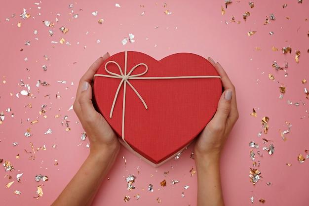 Caja de regalo de forma de corazón rojo en rosa festivo, en manos femeninas Foto Premium