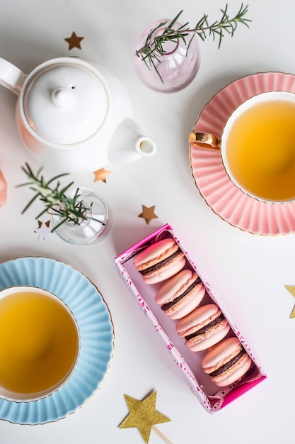 Caja de regalo con macarrones rosas entre tazas de té verde, estrellas y pequeños jarrones. Foto Premium