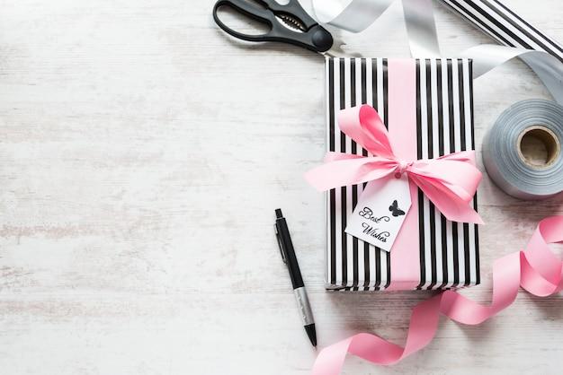 Caja de regalo y materiales de embalaje en un fondo antiguo de madera blanca Foto Premium