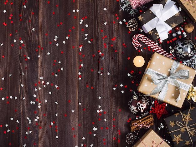 Caja de regalo navideña en una mesa festiva decorada con conos de pino bola de vela de bastón de caramelo Foto gratis