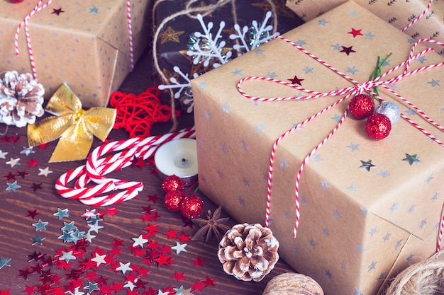 Caja de regalo navideña en una mesa festiva decorada con piñas de caña de caramelo y estrellas de destellos sobre fondo de madera Foto gratis