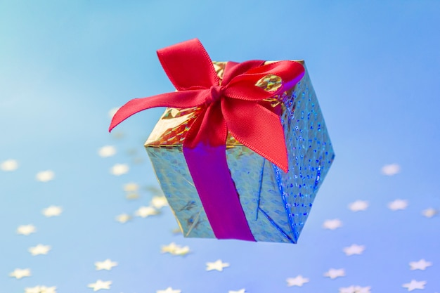 Caja de regalo de oro con cinta roja flotando sobre fondo azul con estrellas brillantes Foto Premium