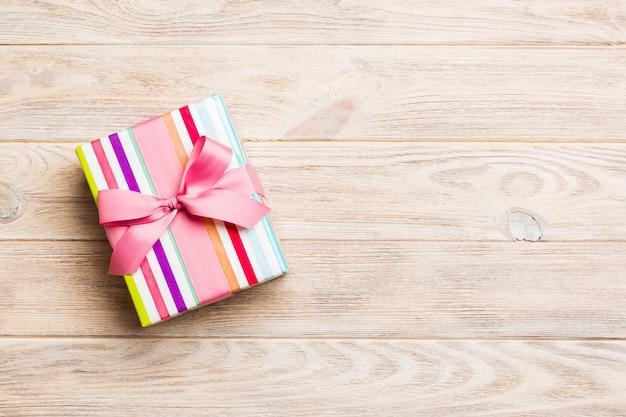 Caja de regalo de papel con cinta de color sobre fondo de madera naranja. vista superior con espacio de copia concepto de vacaciones de navidad Foto Premium