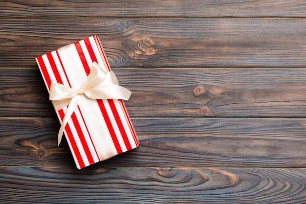 Caja de regalo de papel con cinta de color sobre fondo de madera oscura. vista superior con espacio de copia concepto de vacaciones de navidad Foto Premium