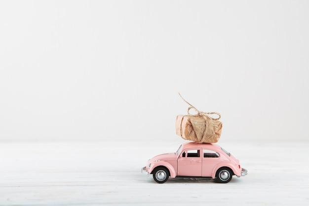 Caja de regalo pequeña en coche de juguete rosa Foto gratis
