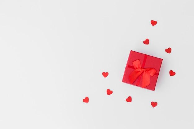 Caja de regalo con pequeños corazones en mesa. Foto gratis