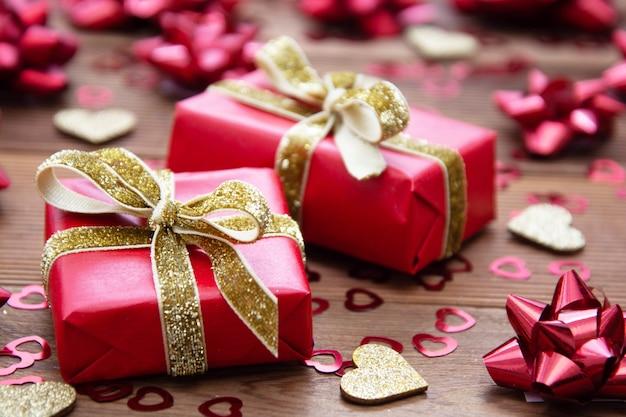 Caja de regalo roja con arcos, en mesa de madera. copia espacio san valentín, cumpleaños, navidad. Foto Premium