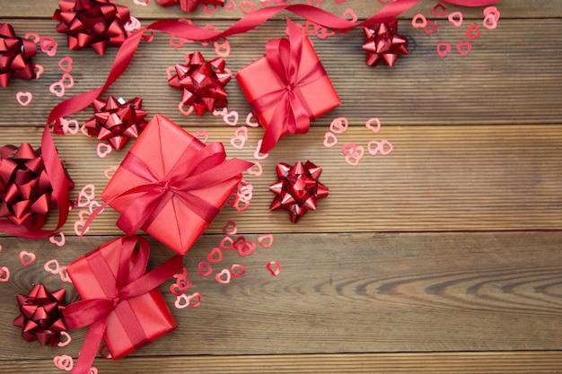 Caja de regalo roja con arcos, sobre fondo de madera. copia espacio san valentín, cumpleaños, navidad. Foto Premium