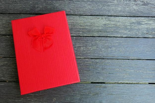 Una caja de regalo roja con cinta roja sobre el fondo negro de madera Foto Premium