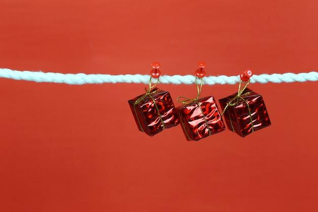 Caja de regalo roja colgar en el tendedero. Foto Premium