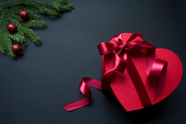 Caja de regalo roja en forma de corazón con cinta roja y ramas de árbol de navidad decoradas Foto Premium