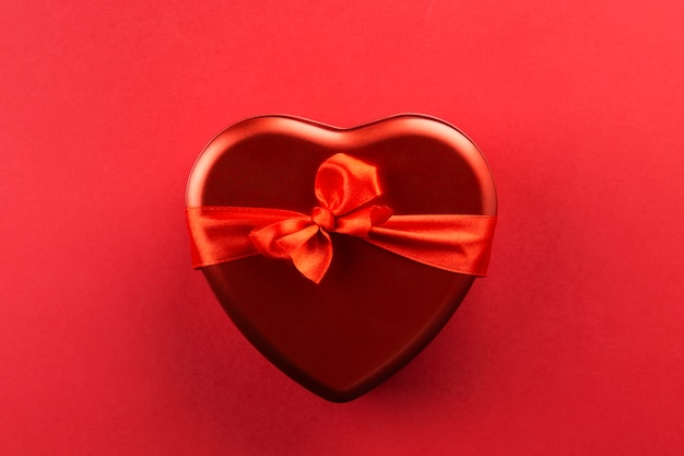 Caja roja en forma de corazón con cinta sobre fondo rojo. Foto Premium