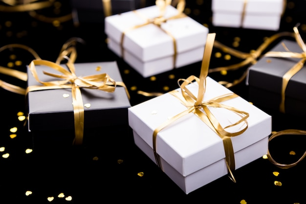 Cajas de regalo en blanco y negro con cinta dorada sobre fondo de brillo Foto Premium