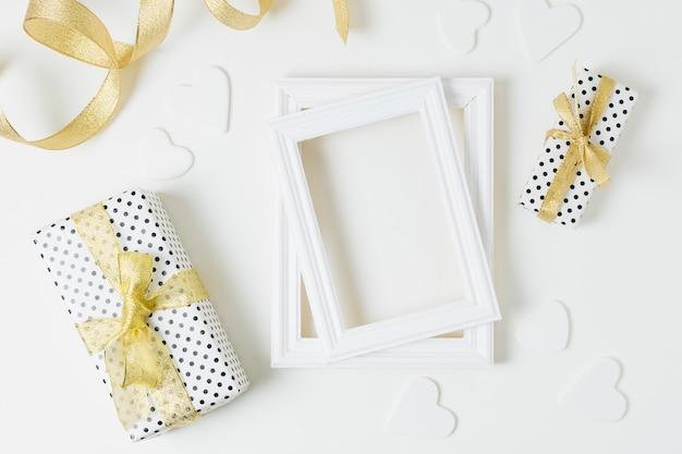 Cajas de regalo envueltas con formas de corazón y marcos de madera para bodas sobre fondo blanco Foto gratis