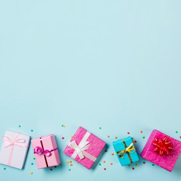Cajas de regalo envueltas y rociadas en el fondo de fondo azul Foto gratis