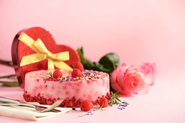 Cajas de regalo en forma de corazón, rosas, tarta de frambuesas con bayas frescas, romero y flores secas. concepto del día de san valentín presente con amor Foto Premium