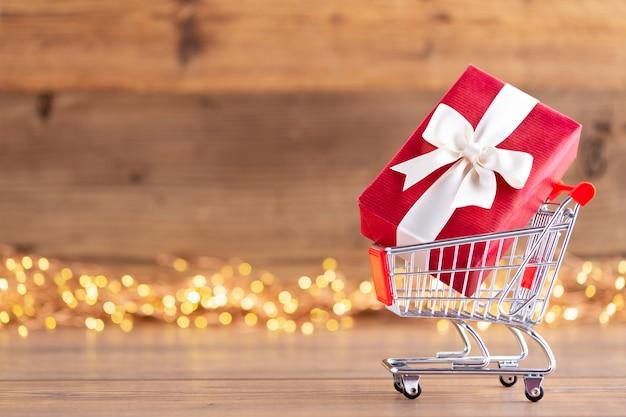 Cajas de regalo de navidad con cintas en un carrito de compras Foto Premium