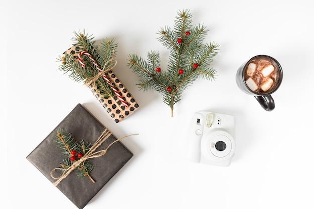 Cajas de regalo con ramas de abeto y taza de café. Foto gratis