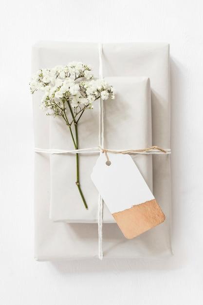 Cajas de regalo y ramitas de flores de aliento para bebés atadas con una cuerda y una etiqueta Foto gratis