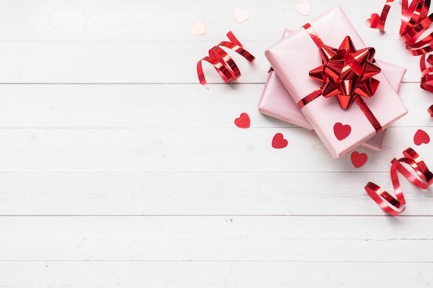 Cajas de regalo rosa con cintas rojas y lazos, corazones de confeti sobre un fondo blanco. copia espacio lay flat. tarjeta de felicitación para fiesta de cumpleaños, boda de san valentín. Foto Premium