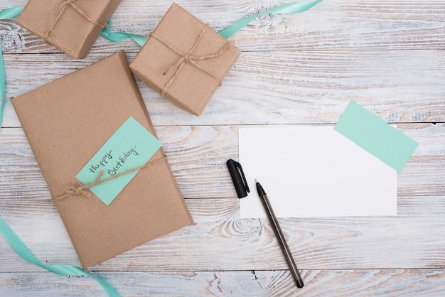 Cajas con regalos de cumpleaños y papel sobre mesa de madera. Foto gratis