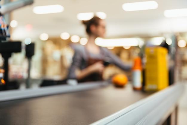 Cajera joven escaneando artículos de supermercado Foto gratis