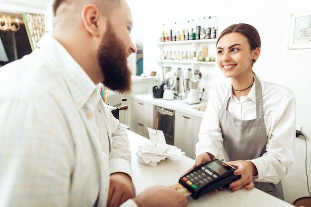 Cajero alegre utilizando dispositivo digital de pago. Foto Premium