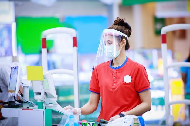 Cajero de supermercado femenino en máscara protectora médica y careta trabajando en supermercado. concepto de coronavirus Foto Premium