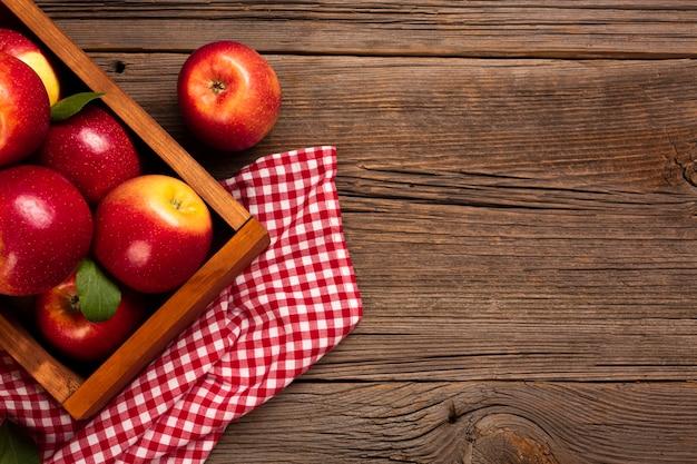 Cajón plano con manzanas maduras con copyspace. Foto gratis