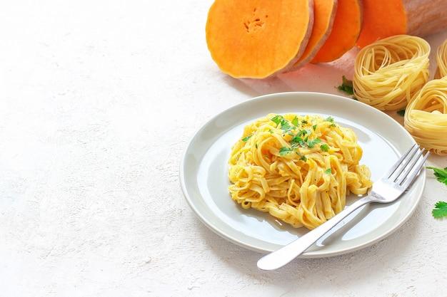 Calabaza alfredo fettucine pasta en un plato de cerámica con rodajas de calabaza cruda fresca. comida de otoño para el almuerzo. receta de calabaza moscada. Foto gratis