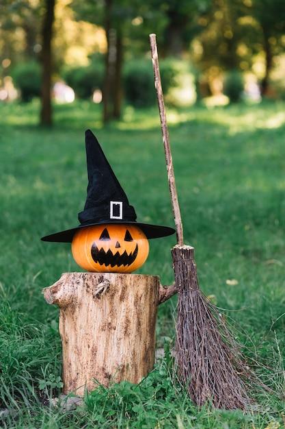 Calabaza espeluznante de halloween con sombrero en tocón cerca de escoba Foto gratis
