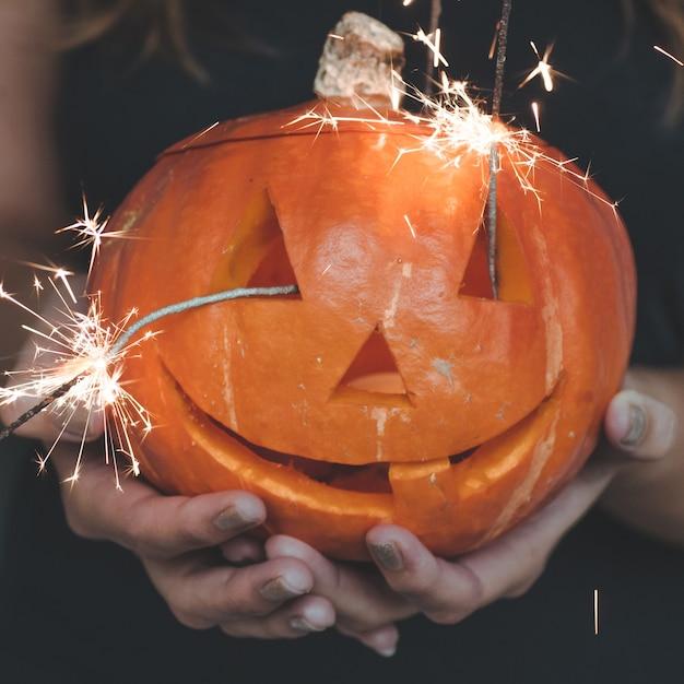 Calabaza de halloween en manos de una niña con luces de bengala. concepto de vacaciones de halloween. bella mujer con calabazas. Foto Premium