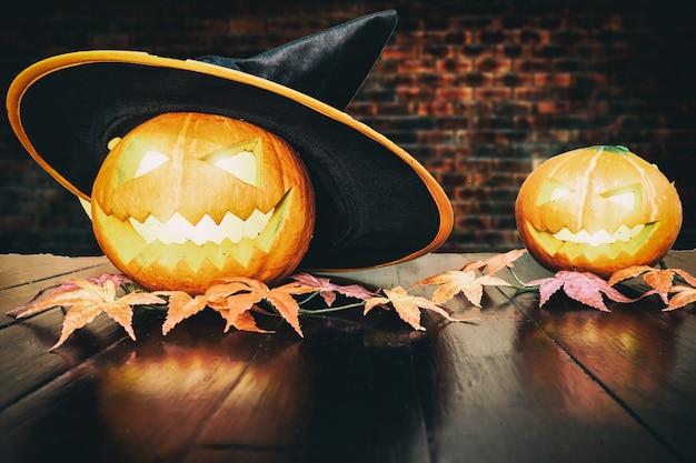 Calabaza de halloween en la tabla de madera negra con el fondo del ladrillo. concepto de vacaciones de halloween Foto Premium