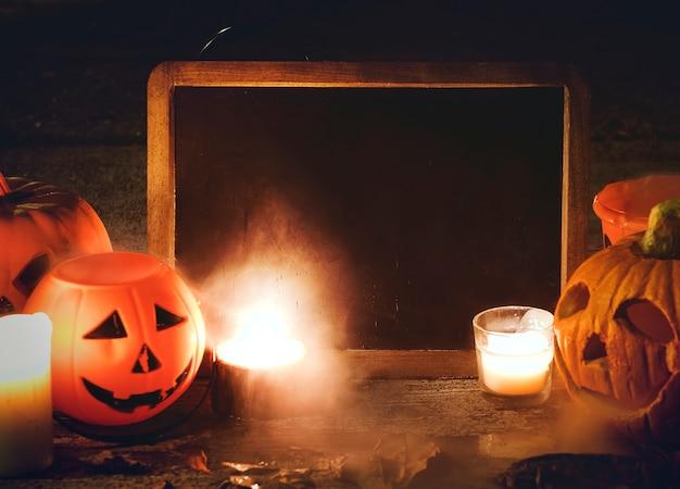 Calabazas de halloween y velas con pizarra Foto gratis