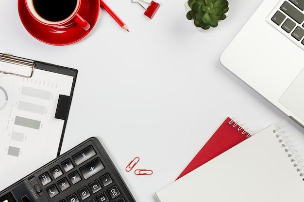Calculadora, computadora portátil, bloc de notas en espiral, taza de café, planta de cactus en el escritorio blanco Foto gratis