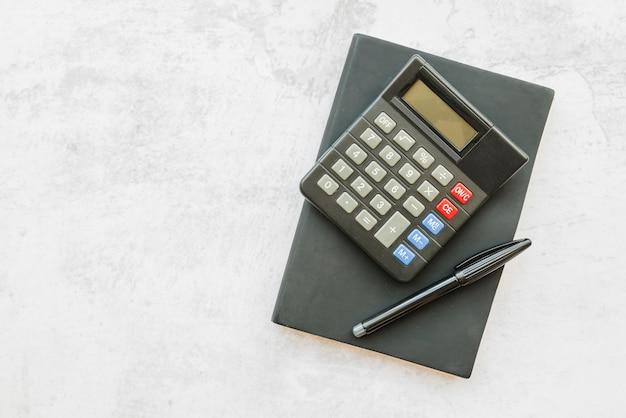 Calculadora con cuaderno sobre mesa Foto Premium