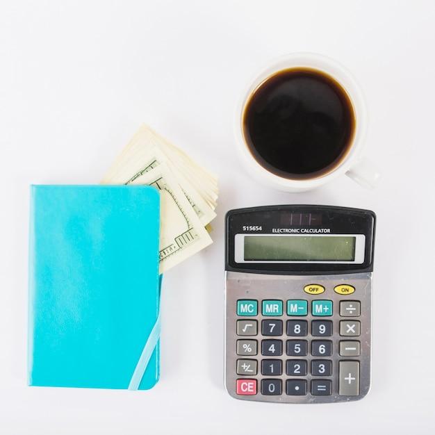 Calculadora con dinero en el cuaderno en la mesa Foto gratis