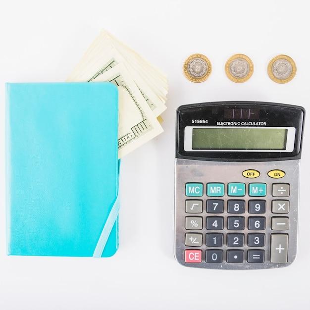 Calculadora con dinero y cuaderno en la mesa Foto gratis