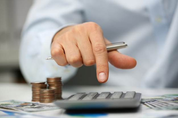 La calculadora plateada de la llave de empuje de mano masculina miente Foto Premium