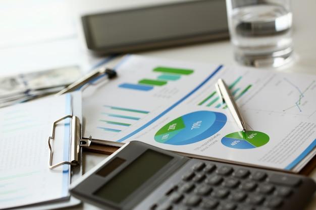 La calculadora plateada con teclado gris yace en el gráfico de escritorio y en la configuración de la oficina. cálculo de gastos familiares ingresos sociales población independiente concepto de investigación de crecimiento de situación de irs Foto Premium