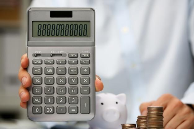 Calculadora de retención de mano masculina en casa Foto Premium