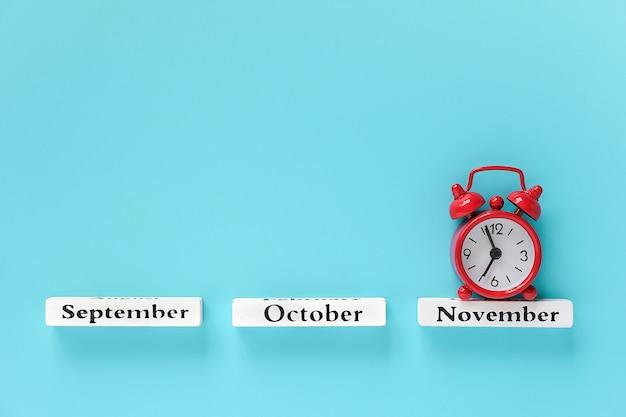 Calendario de madera meses de otoño y despertador rojo en noviembre Foto Premium