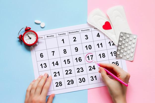 Calendario de la menstruación con almohadillas, reloj despertador, píldoras anticonceptivas hormonales. Foto Premium